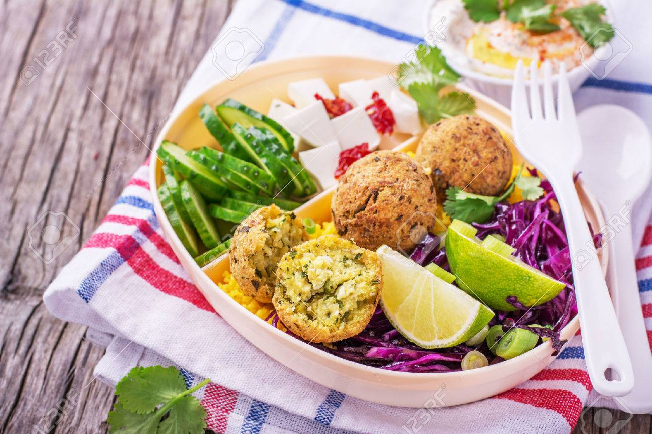 Box Lunch on the road for a picnic or to the office for lunch with cous cous, falafel chick peas, red cabbage salad, slices of cucumber, feta cheese and salad hummus in a white plastic container with a fork and spoon decorated with sprigs of cilantro. sel - 51977481