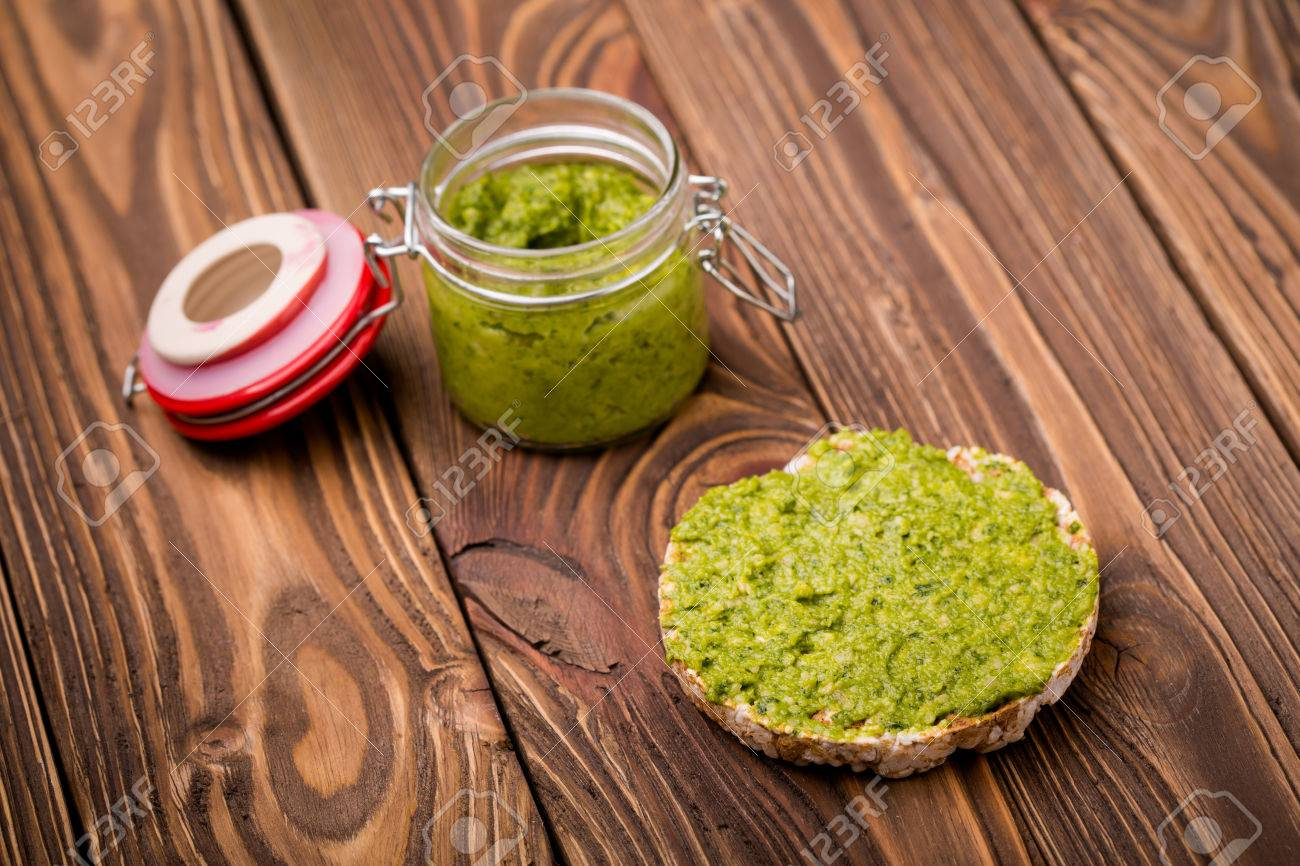 Natural homemade DIY vegan very healthy green pesto made of radish leaves and nutritional yeast flakes on a rice waffle in a glass jar on a wooden table - 48379864
