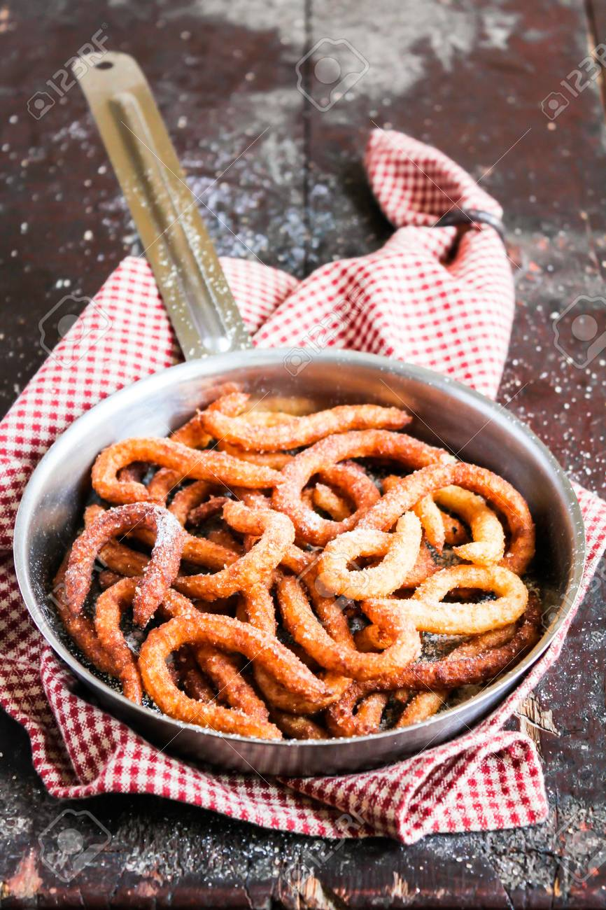 Cooking pan with traditional spanish dessert churros with chocolate