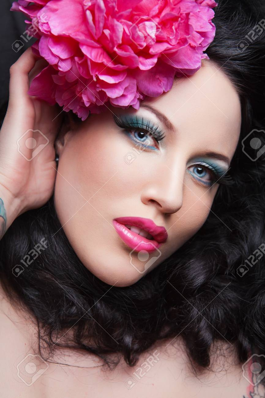 Young beautiful brunette girl with pink flower in her hair. pink flower Stock Photo - 16334027