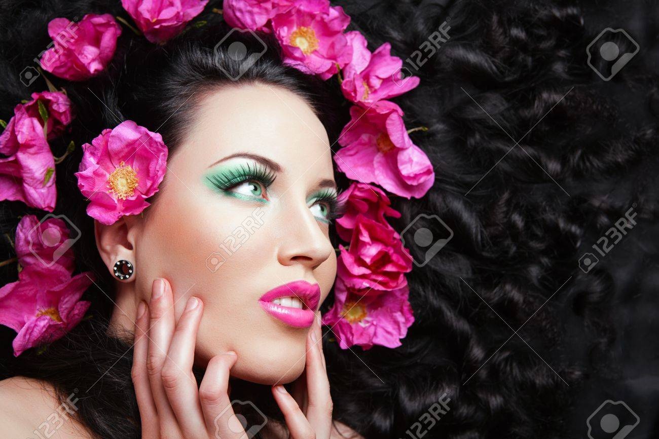 Young beautiful brunette  girl with pink flowers in her hair. pink flower Stock Photo - 16334028