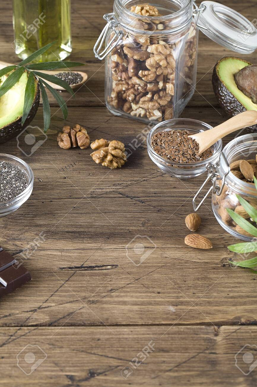 healthy fats sources flax nuts oil avocado chia seeds and bitter chocolate on brown wood background .healthy food eco friendly concept, copy space - 149021534