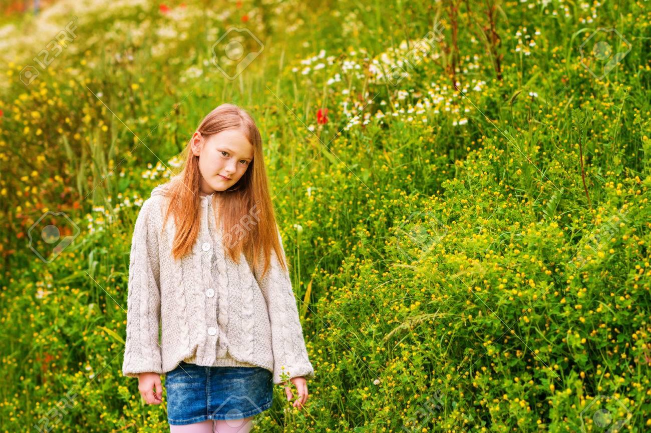 Retrato al aire libre de la adorable niña de 8 9 años de edad, vistiendo chaqueta de punto beige, posando en el campo verde