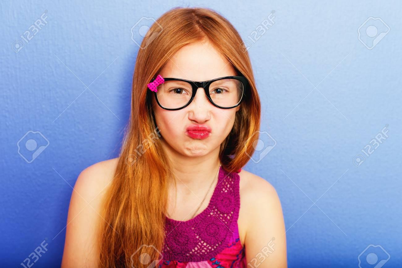 cb2346c6e4 Banque d'images - Prise de studio d'une jeune fille de 9 à 10 ans avec  lunettes de vue, debout contre un fond violet bleu
