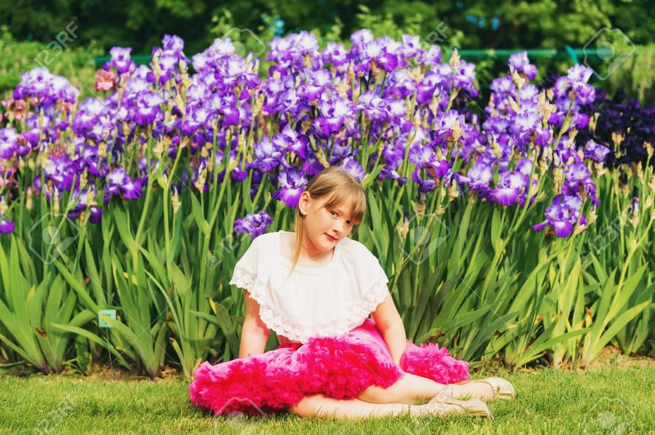 Cute little girl playing in iris flower garden on a nice summer cute little girl playing in iris flower garden on a nice summer day wearing white izmirmasajfo