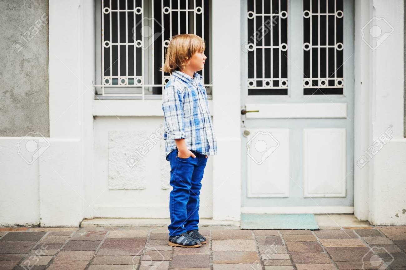 Retrato De Moda Al Aire Libre De Lindo Nino De 6 Anos Vistiendo Camisa Y Pantalones Casuales De Cuadros Azules Las Manos En Los Bolsillos Fotos Retratos Imagenes Y Fotografia De Archivo