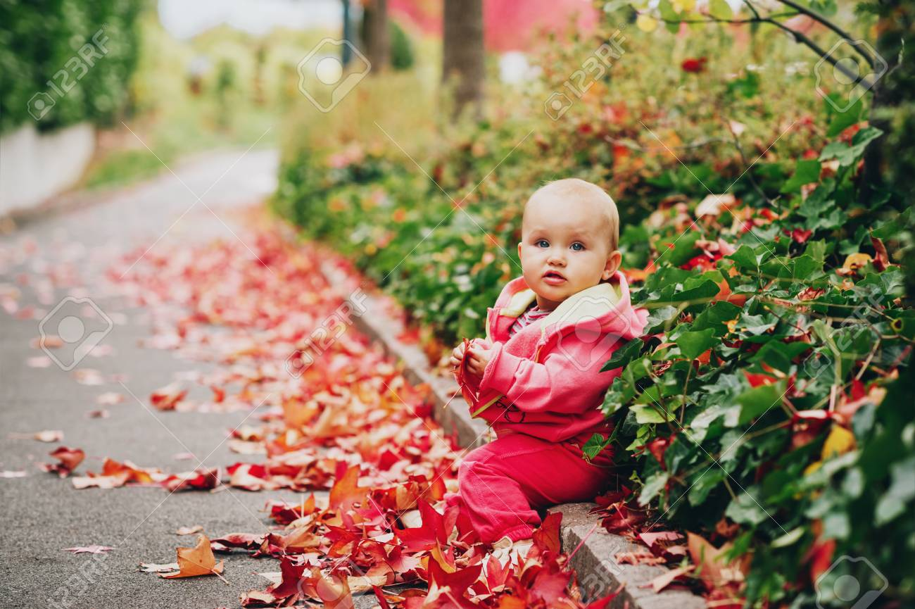 adorable little baby girl of 9-12 month old playing outdoors.. stock