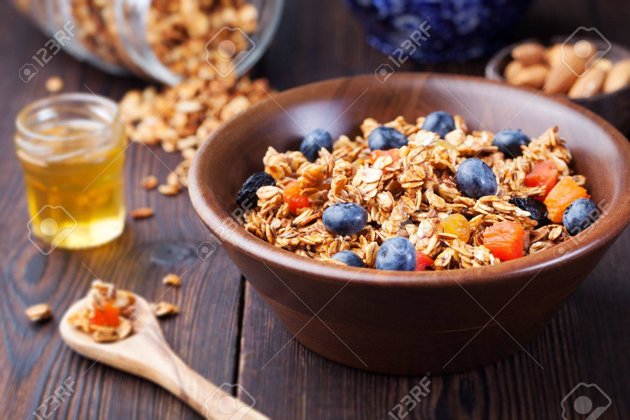 Healthy breakfast. Fresh granola, muesli with berries, honey and milk in a wooden bowl on a wooden background Top view - 53006510