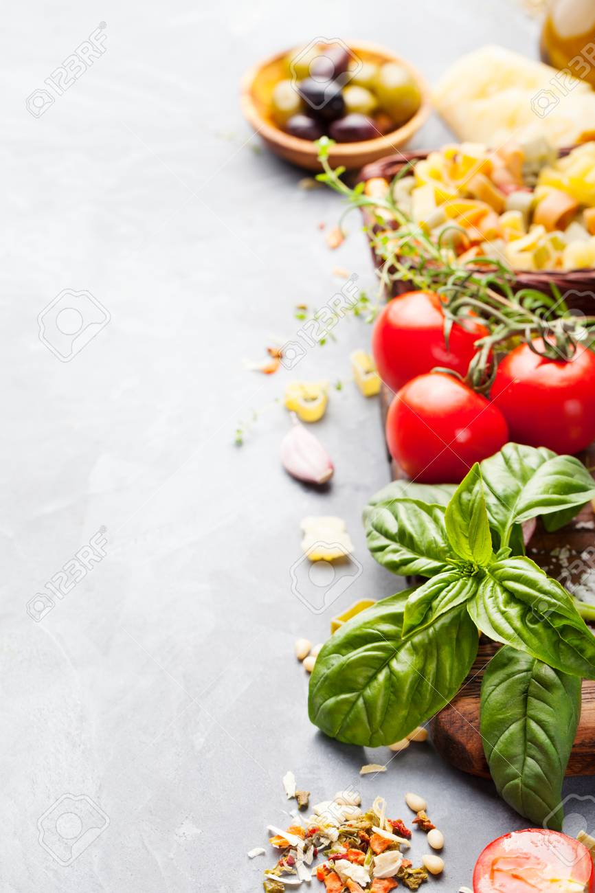 Italian food background with vine tomatoes, basil, spaghetti, olives, parmesan, olive oil, garlic Ingredients on stone table Copy space Top view - 57103064