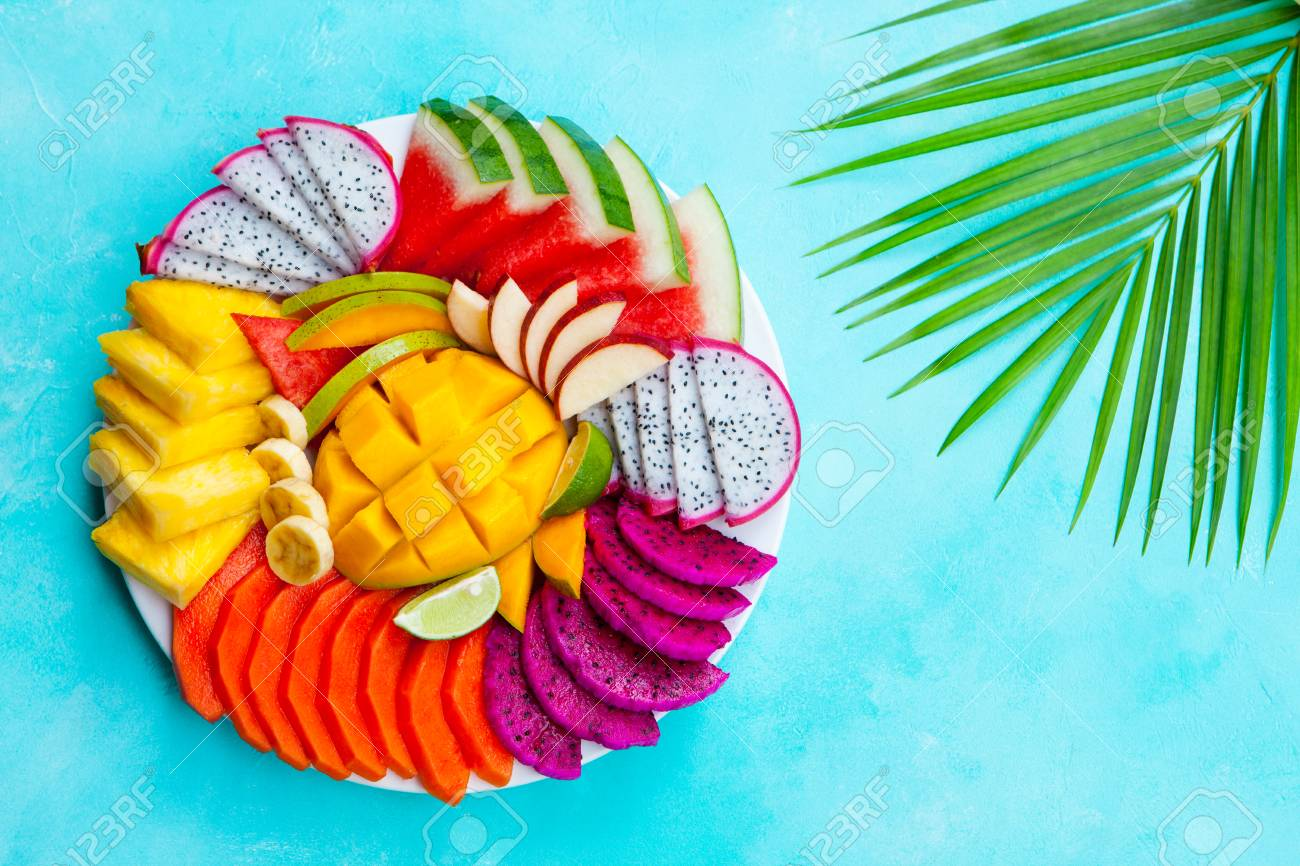 Tropical fruits assortment on a white plate with palm leaf. Blue background. Top view. Copy space. - 122115578