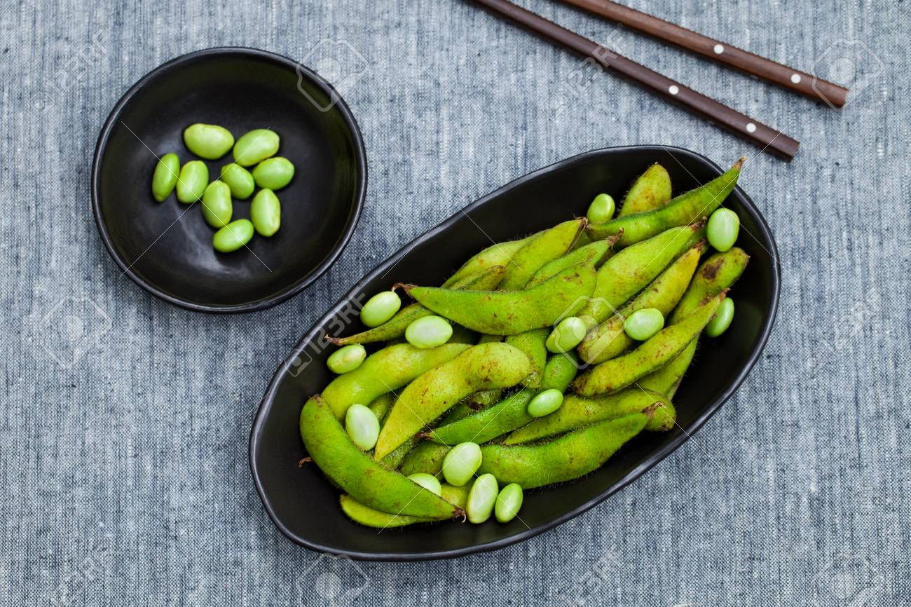 Fresh edamame green beans in black bowl. Grey background. Top view. Copy space. - 122115701