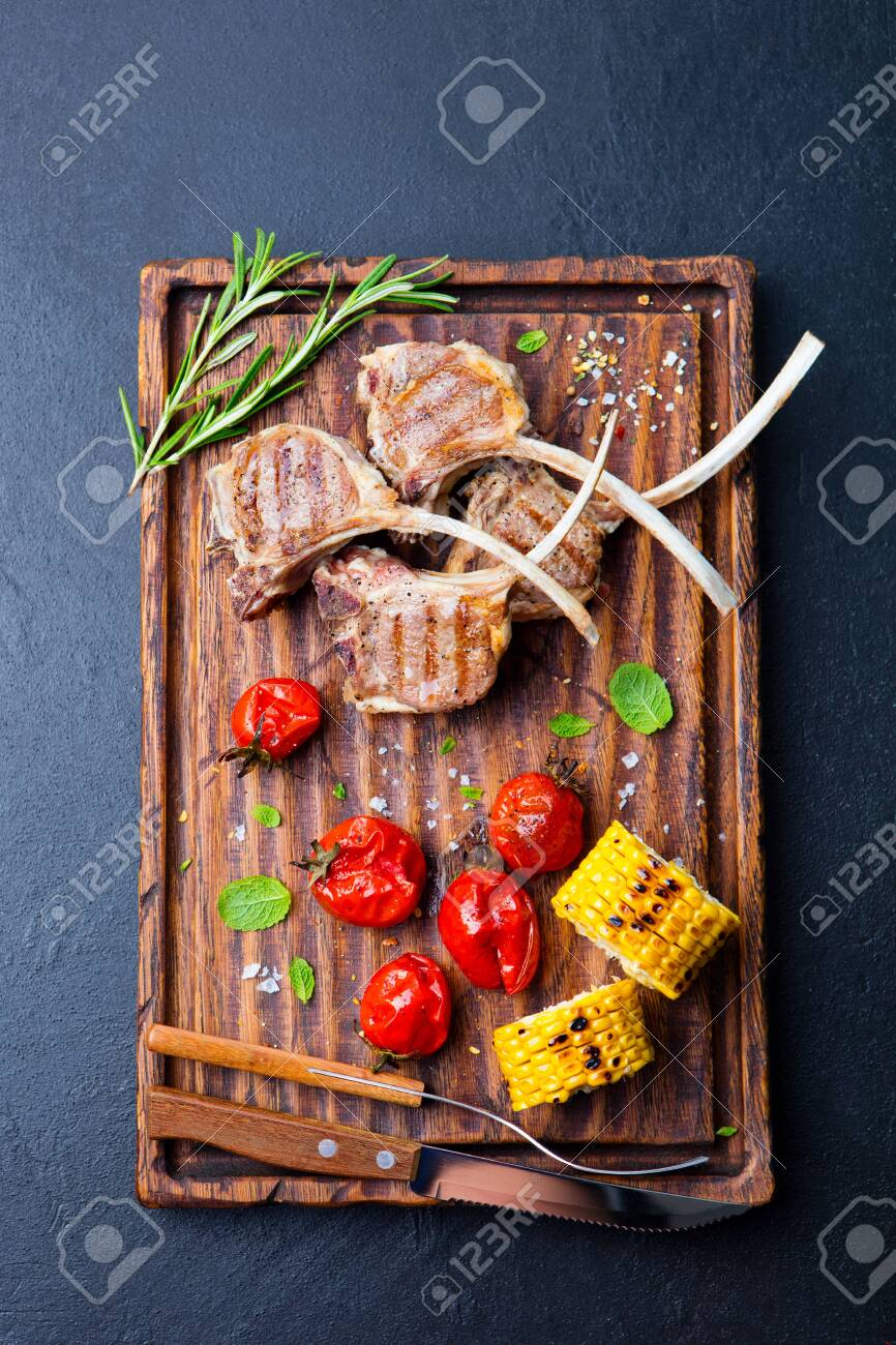 Lamb ribs grilled on cutting board with roasted vegetables. Black background. Top view. - 123507025