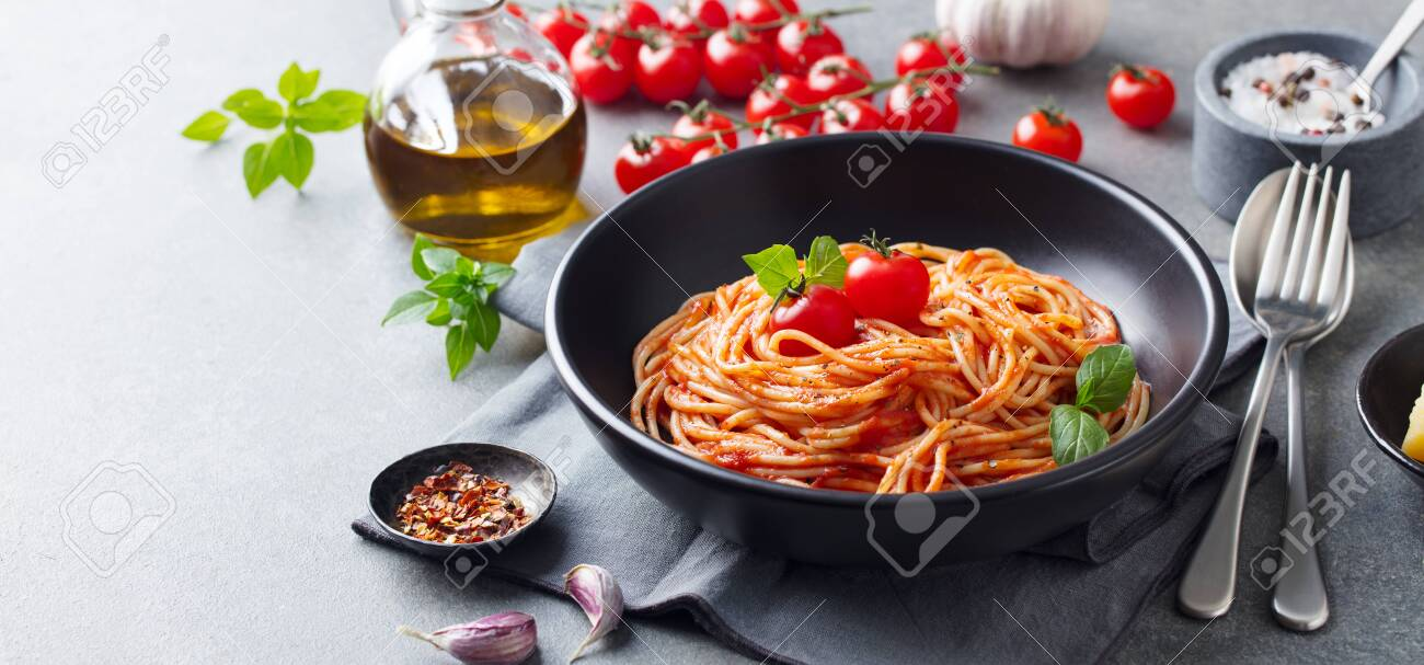 Pasta, spaghetti with tomato sauce in black bowl on grey background. Copy space. - 134708255