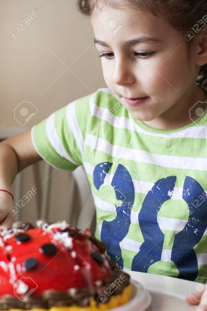 A Little Girl Is Cutting Her Birthday Cake With Knife Standard Bild