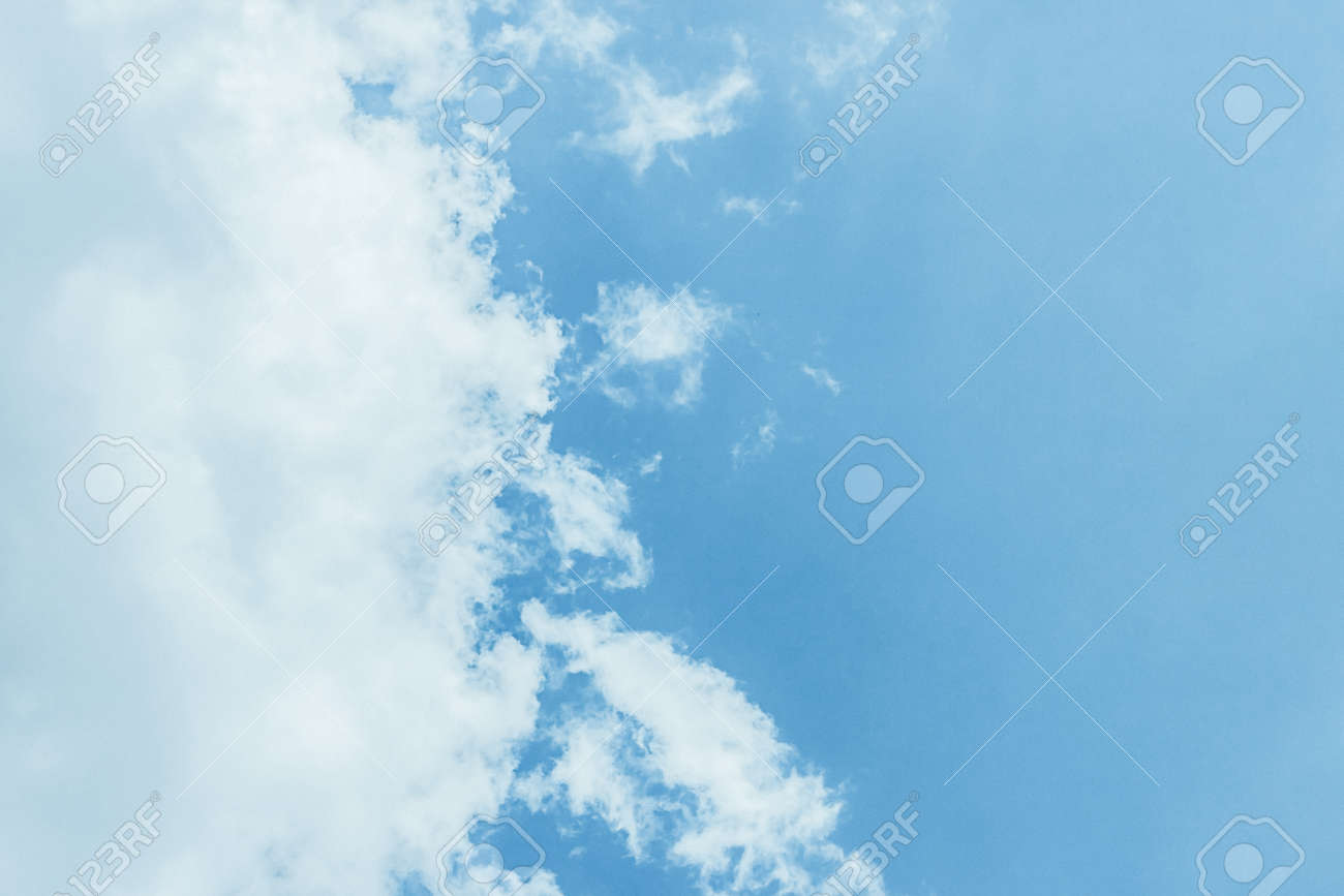 Fluffy white clouds on a clear blue background float in the sky. Divine view. Copy space. - 147922150