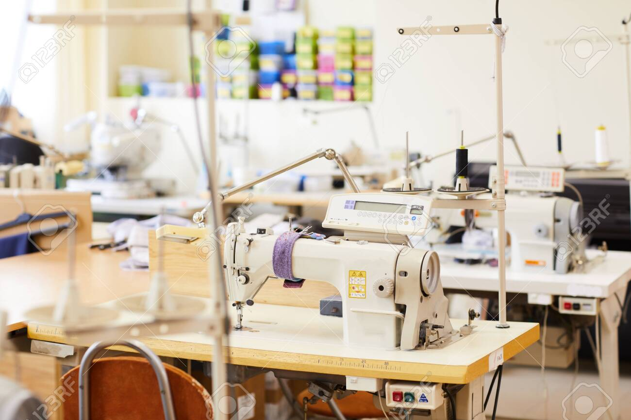 Image of modern sewing machines on work places in workshop - 131663207