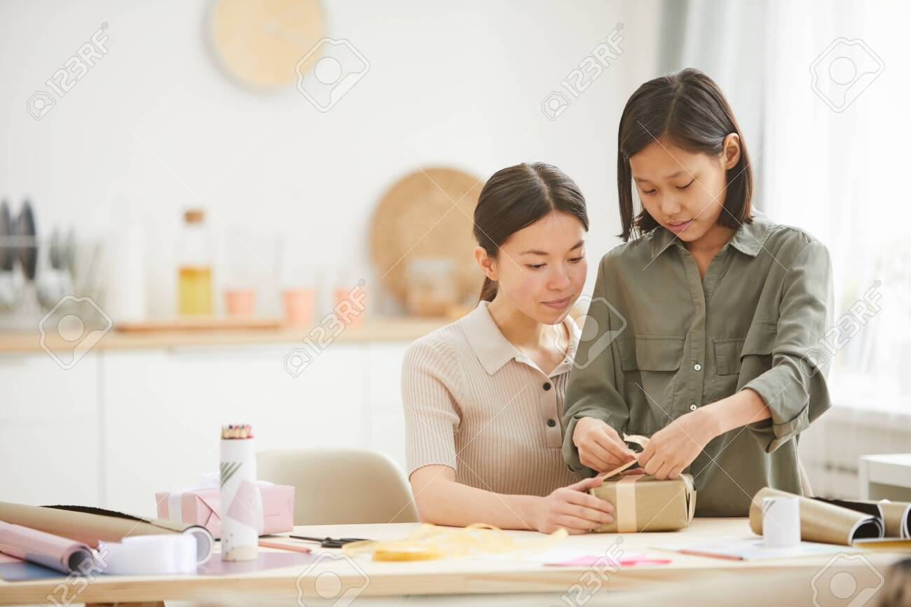 Young Asian woman and teen girl spending time together at hme preparing gifts for Mothers Day holiday, copy space - 141678575