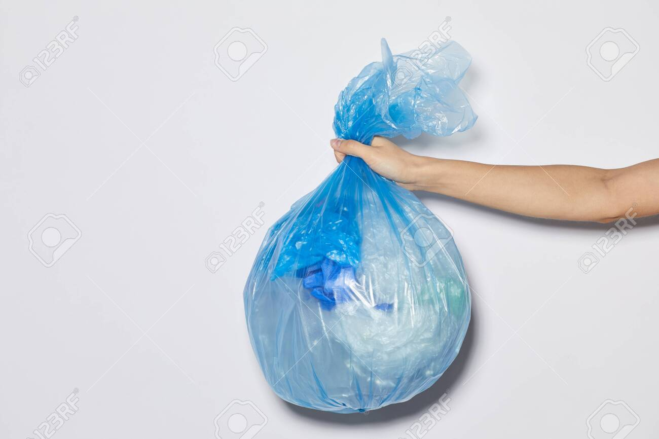 Close-up of female hand holding package with garbage against the white background - 149316530