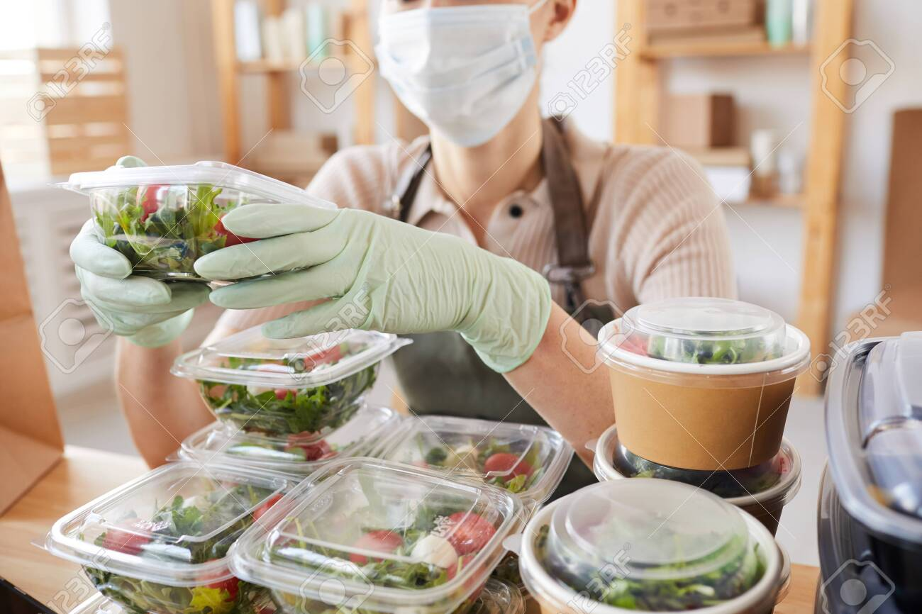 Close-up of young woman in protective mask and gloves packing fresh vegetables in boxes while sitting at the table - 150090558