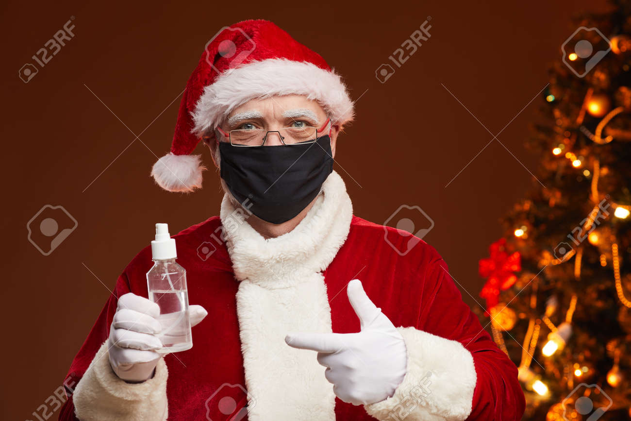 Portrait of Santa Claus in red costume wearing protective mask pointing at antiseptic in his hand standing at studio - 158016479