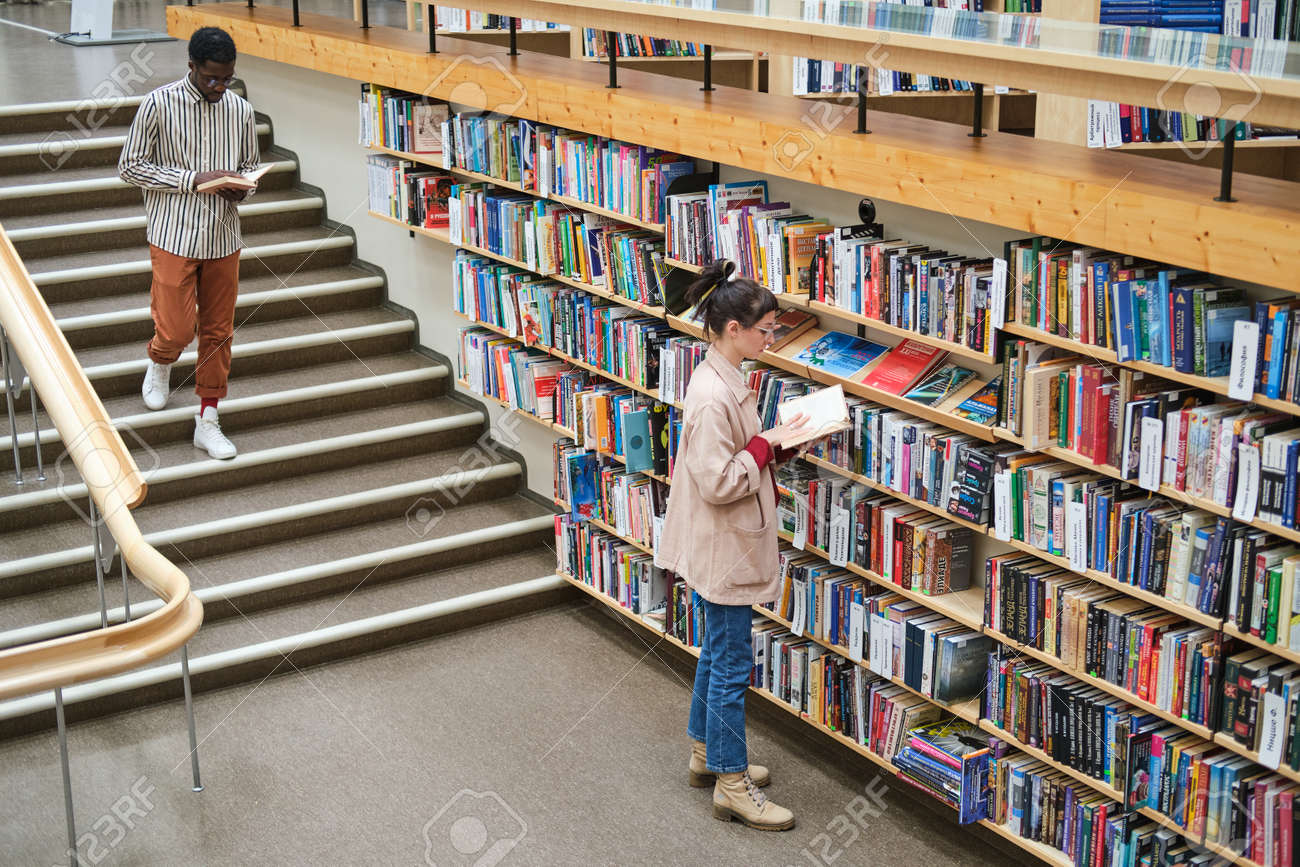 Young people choosing books and reading them in the library - 169720581