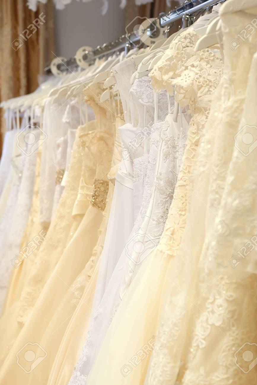 white and cream colored wedding dresses vertical stock photo