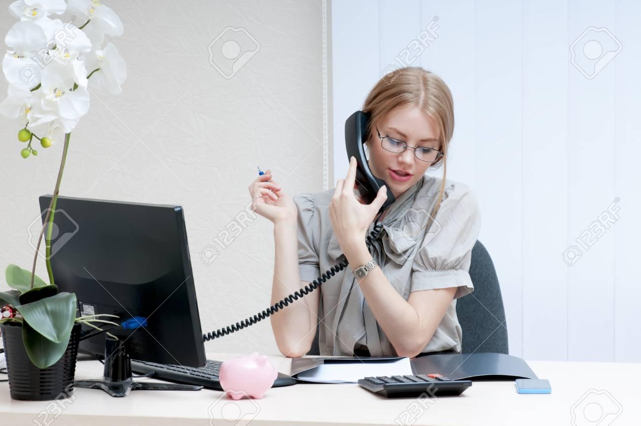 Occupé fille bureau de parler sur le téléphone portable et regarde