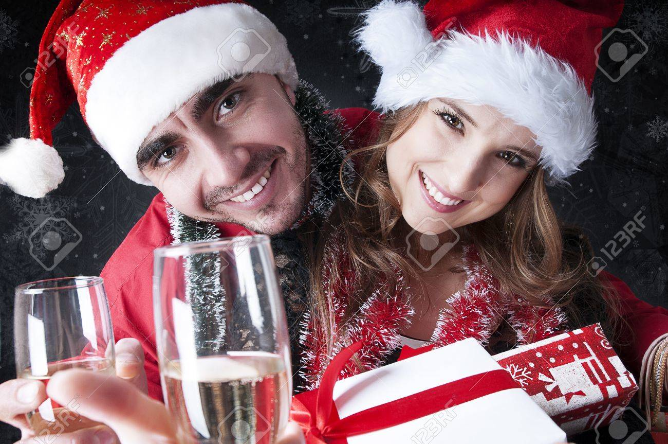 Funny Christmas Couple With Glasses Of Champagne Covering Snowy Background Stock Photo