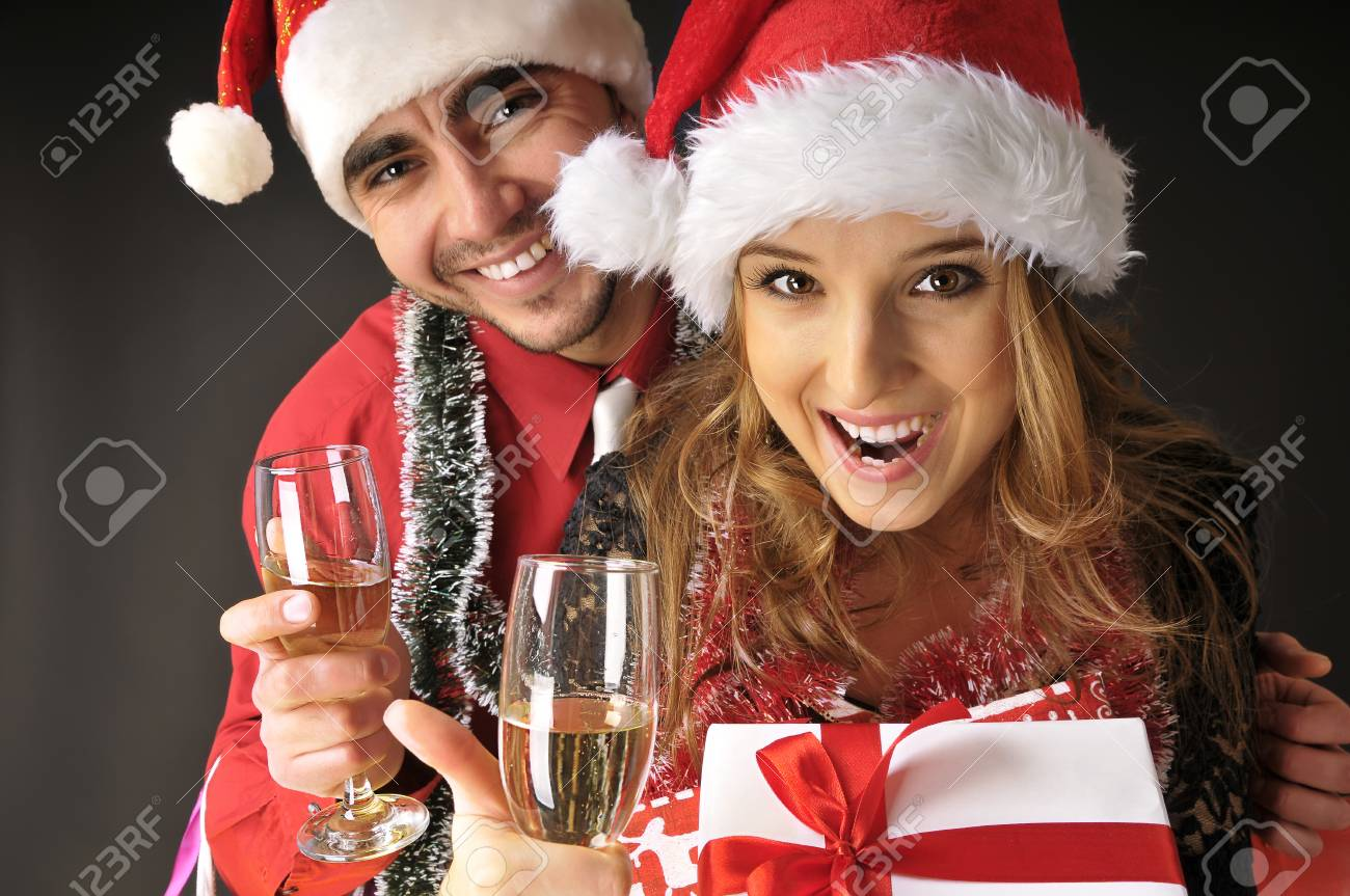 Funny Christmas Couple With Glasses Of Champagne Covering Dark Background Stock Photo
