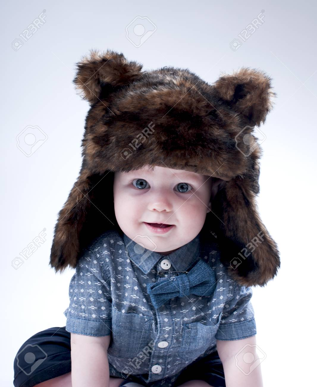 best quality new cheap watch Funny baby boy in a winter fur hat cover gray background.