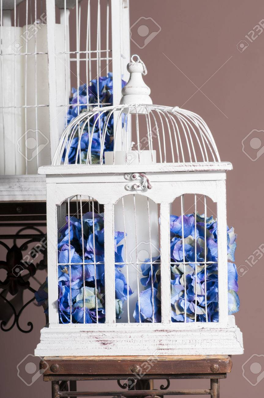 white wooden bird cages with blue hydrangeas and paraffin candle