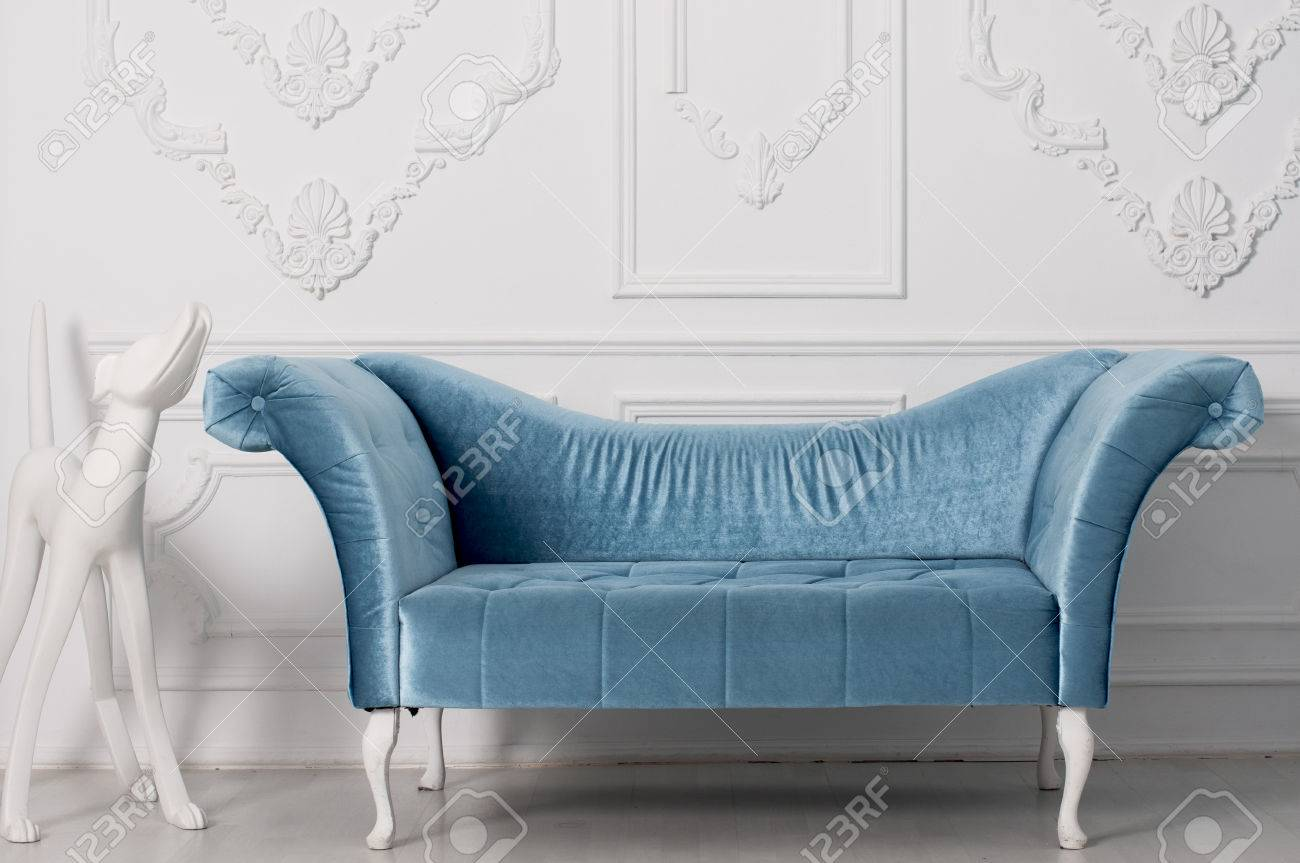 Luxurious Blue Velvet Sofa And And White Sculpture Of A Dog Near The  Armrest Behind A