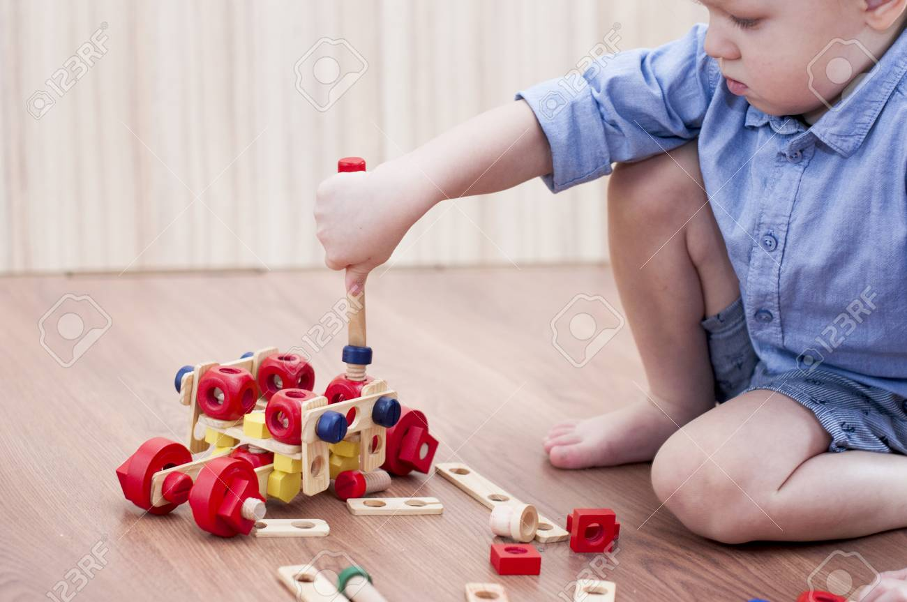 The Little Boy Twists The Bolt With A Screwdriver On Floor Kid Stock Photo Picture And Royalty Free Image Image 94618020