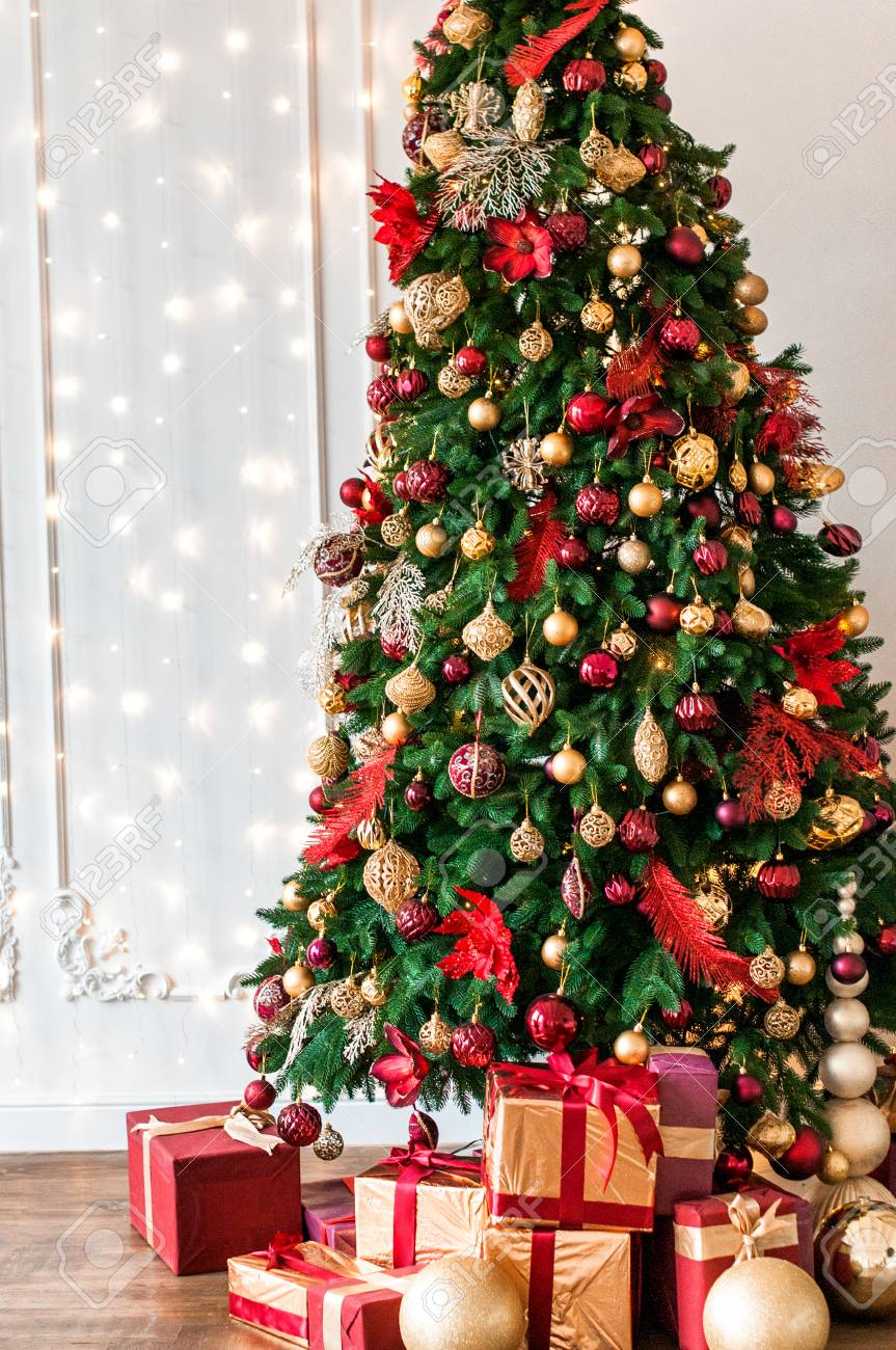 Christmas tree decorated with red and gold toys presents box