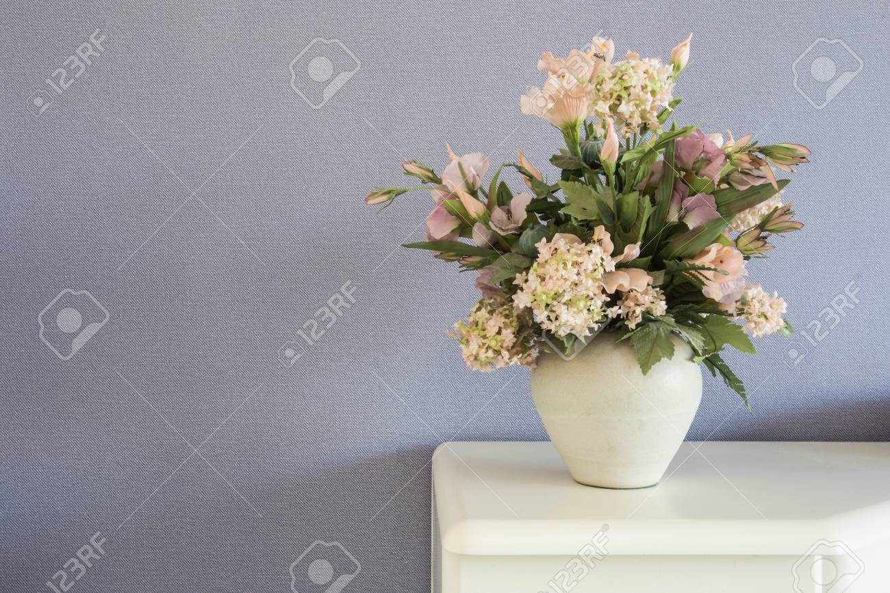 123RF.com & Fake flowers in white vase on the table with purple wall background..