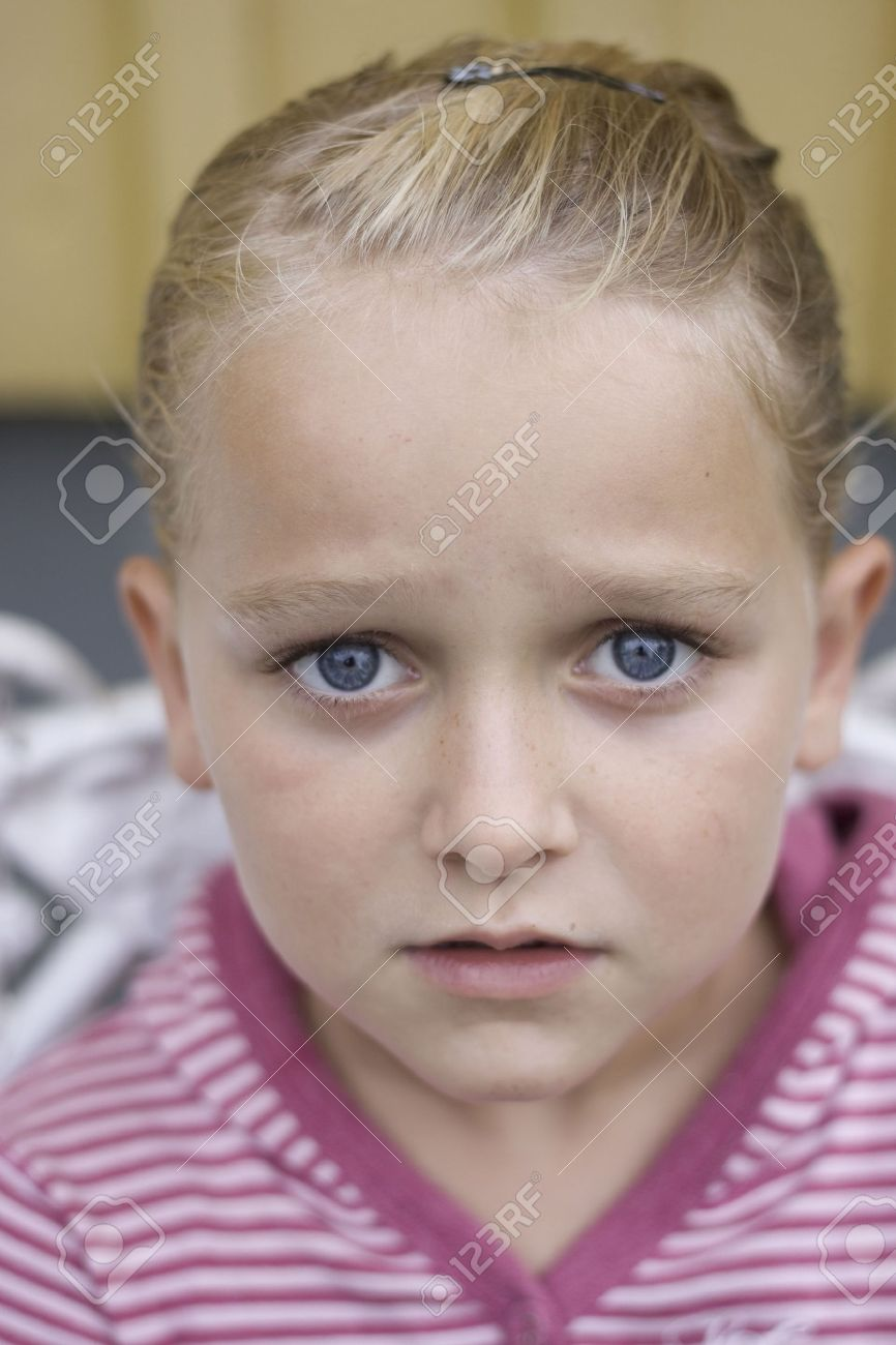 Beautiful with big sad blue eyes looking into the camera. Soft focus Stock Photo - 7756359