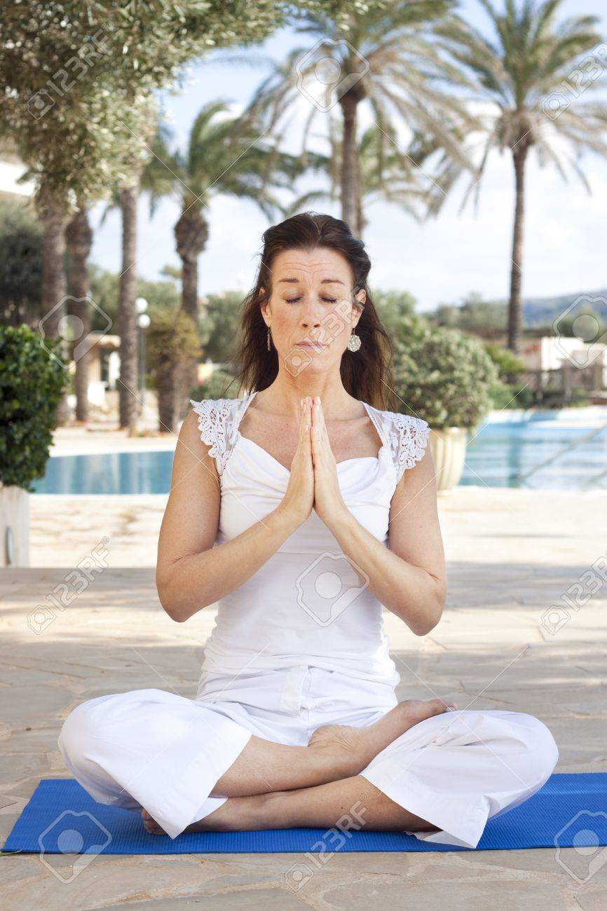 Middle aged lady sitting in a lotus yoga position Stock Photo - 17700425