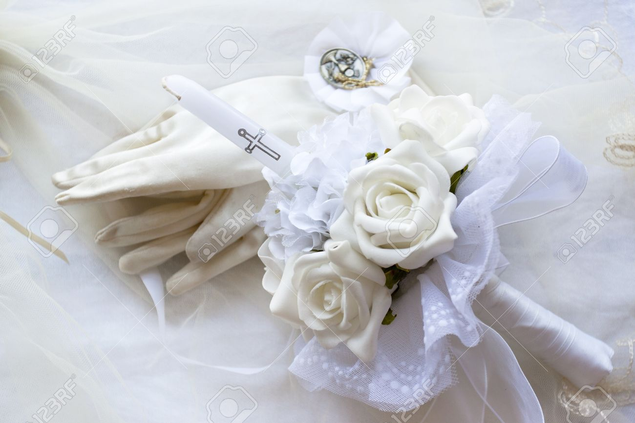 A First Holy Communion Candle With Flowers Gloves And Medal Stock