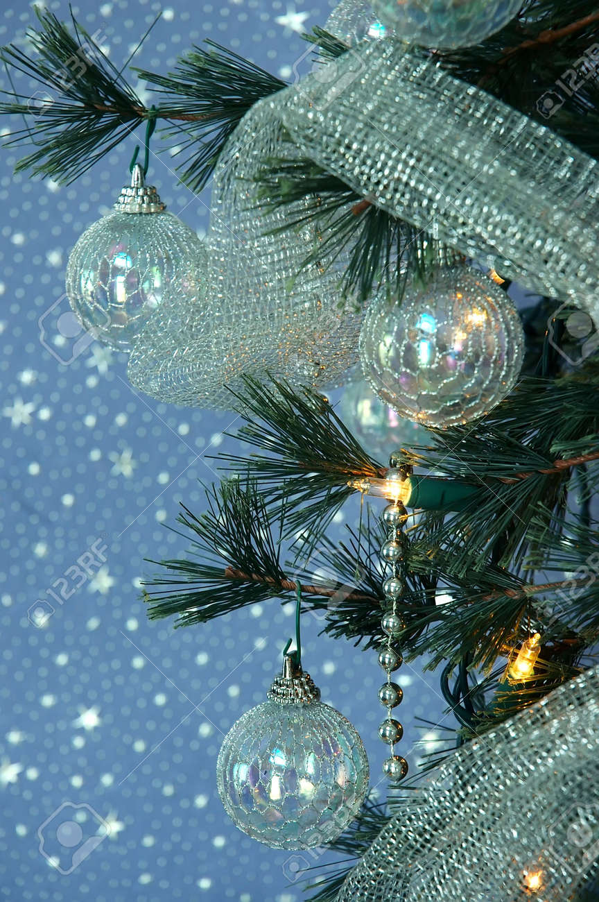 Led christmas tree decoration - Iridescent Ornaments Silver Beads And Glittery Silver Netting Adorn A Lighted Christmas Tree Stock