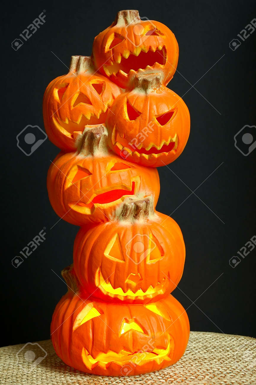 jack o lanterns halloween decoration a stack of pumpkins that have been carved into