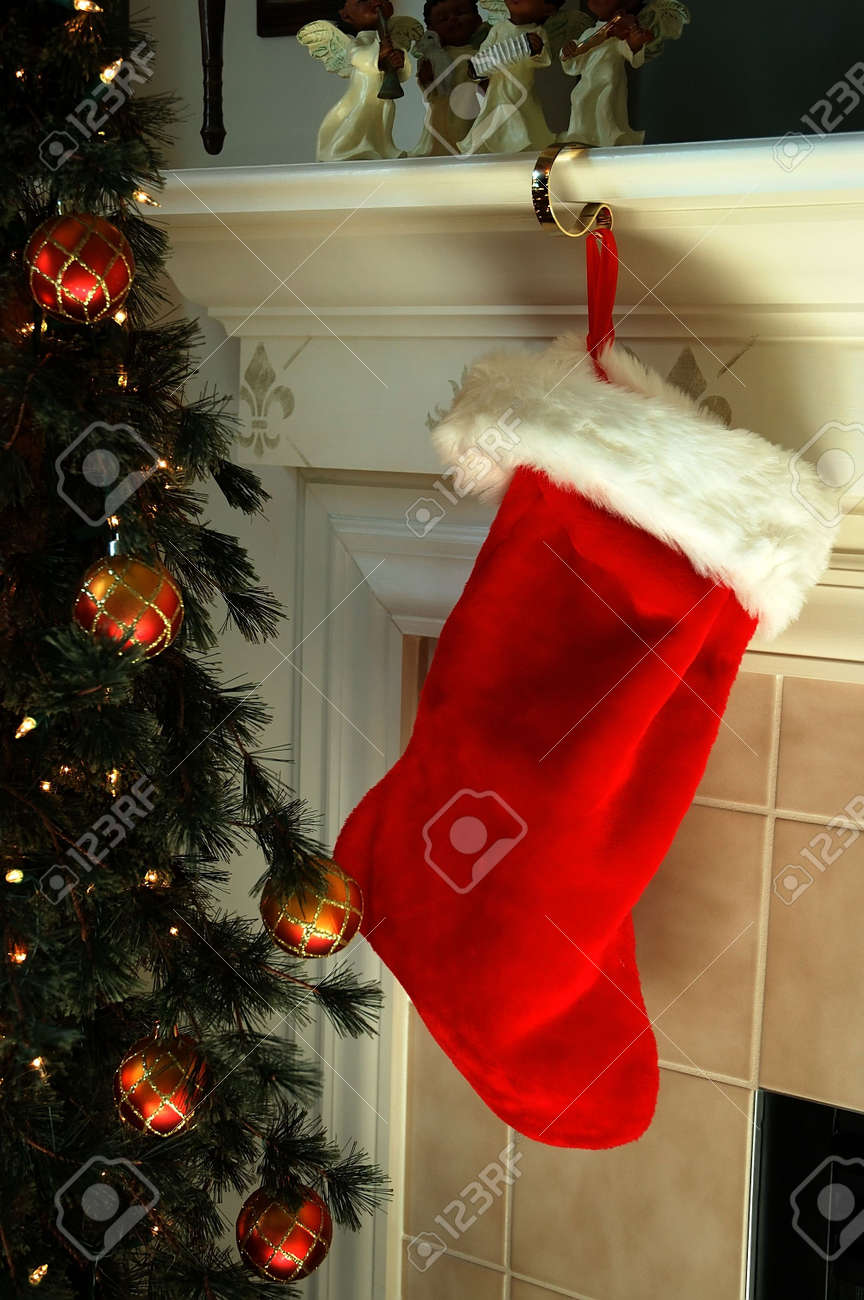 christmas stocking hanging on the fireplace mantle next to the