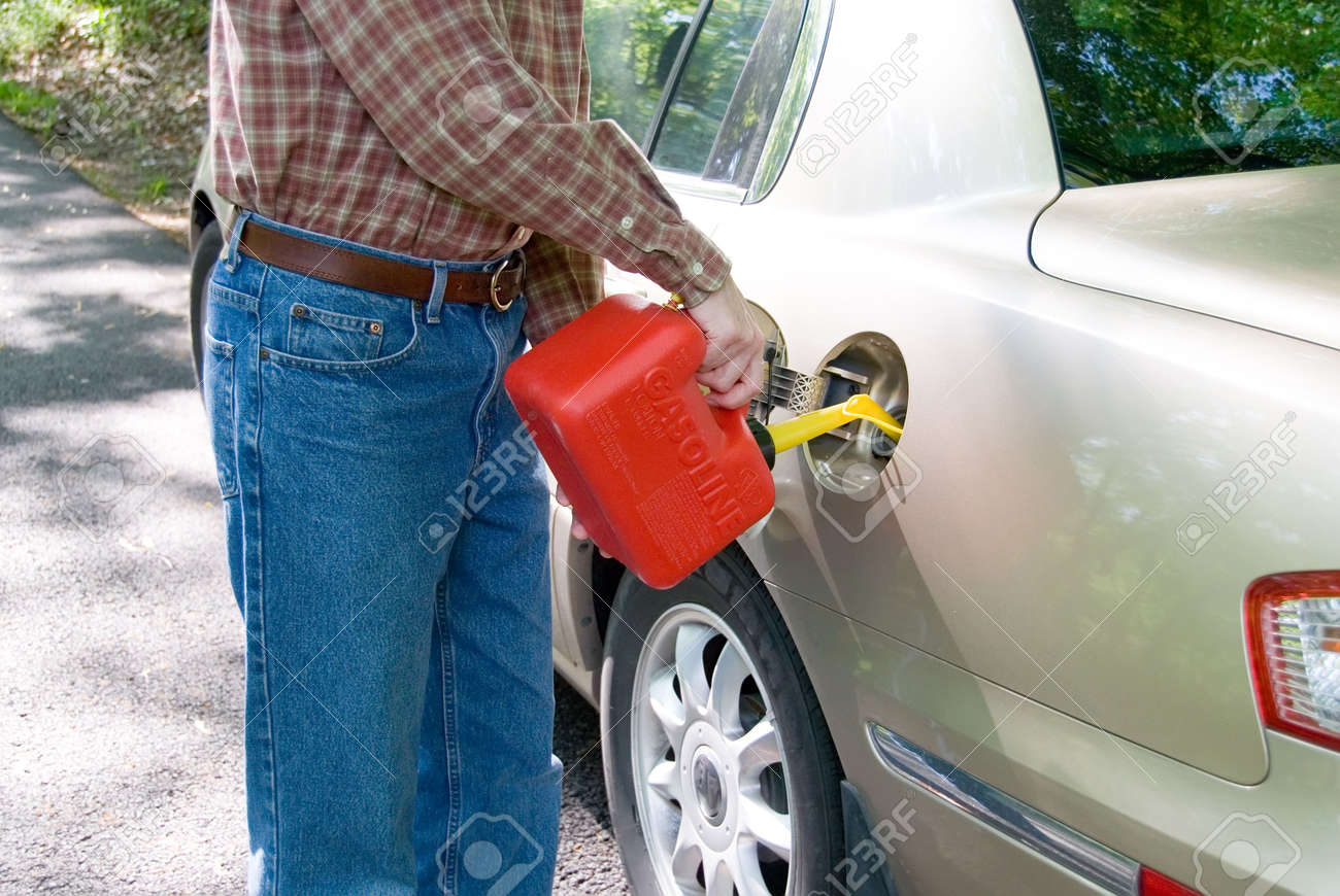 A man pouring gasoline into his tank from a red gas can. Stock Photo - 394601