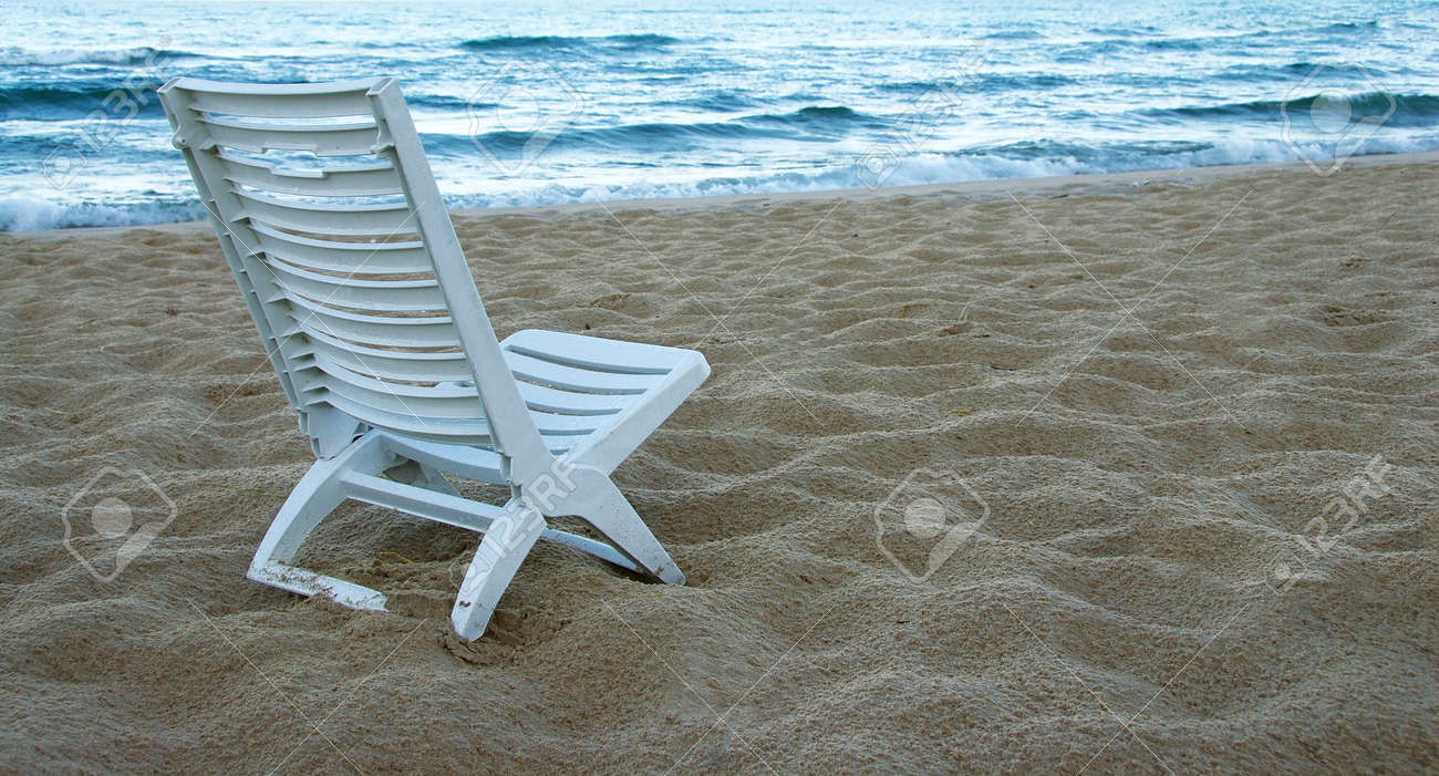 Plastic beach chair - A Deserted Lake Michigan Beach With One White Plastic Chair On The Sand Stock Photo