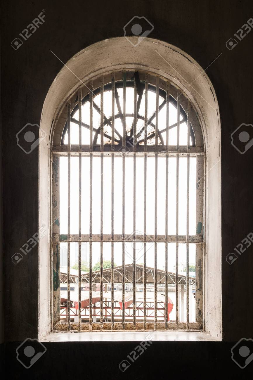 old metal lattice window in the wall of old building stock photo