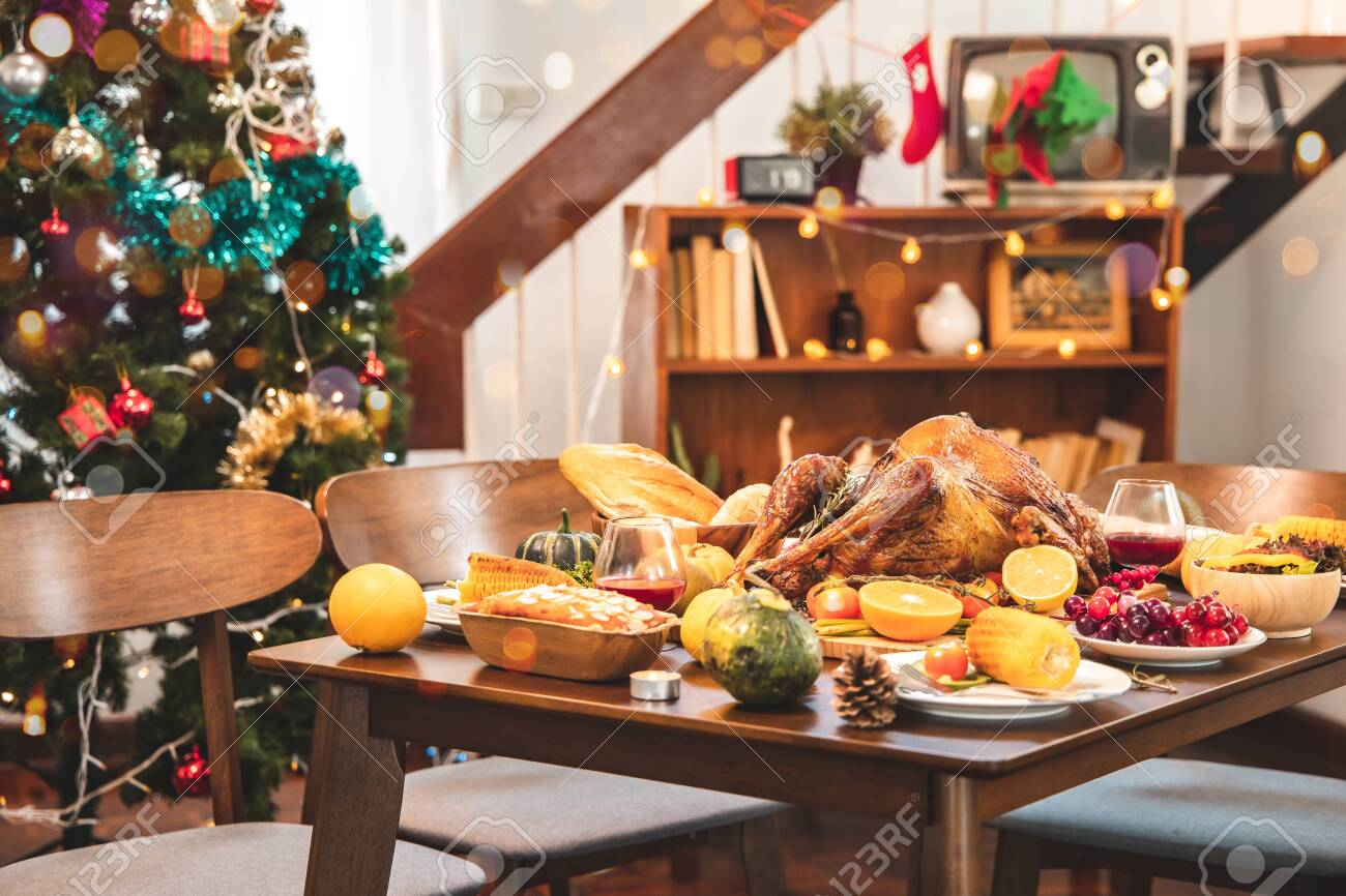 Roasted chicken or turkey with sauce and grilled autumn vegetables: corn,pumpkin on wooden table, top view, frame. Christmas or Thanksgiving Day food concept. - 134656894