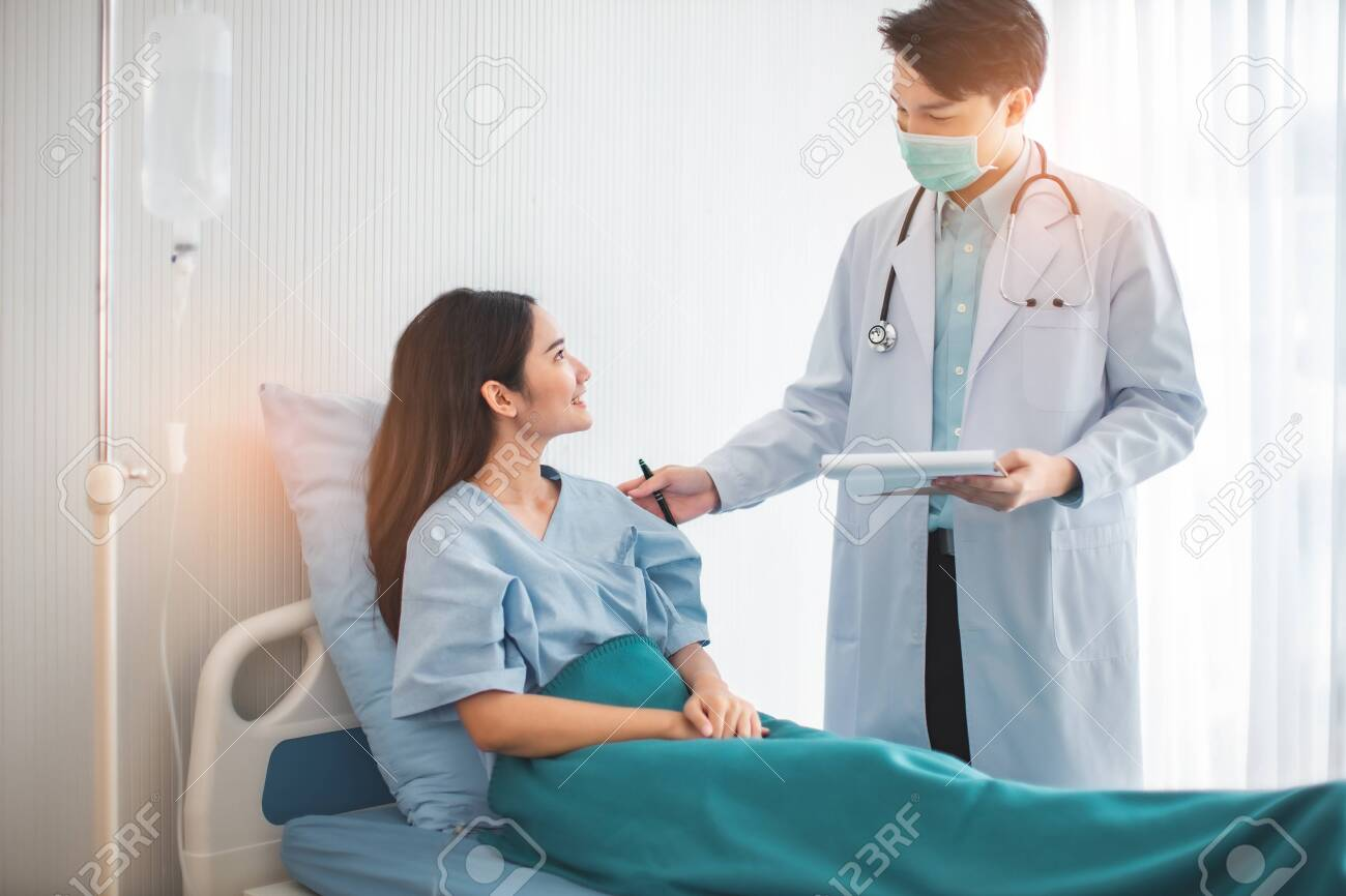 Medicine and health care concept. Asian doctor is taking care patient woman in hospital.doctor or nurse wear protection mask checking and take care infection people from covid-19 . - 146350604