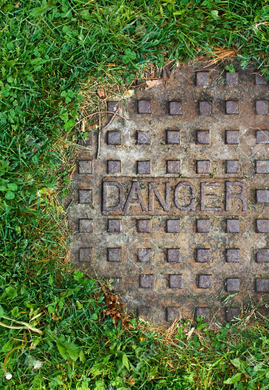 Old sewer manhole with the word danger on it, with green grass around it, alert sign, background, texture Stock Photo - 29184438
