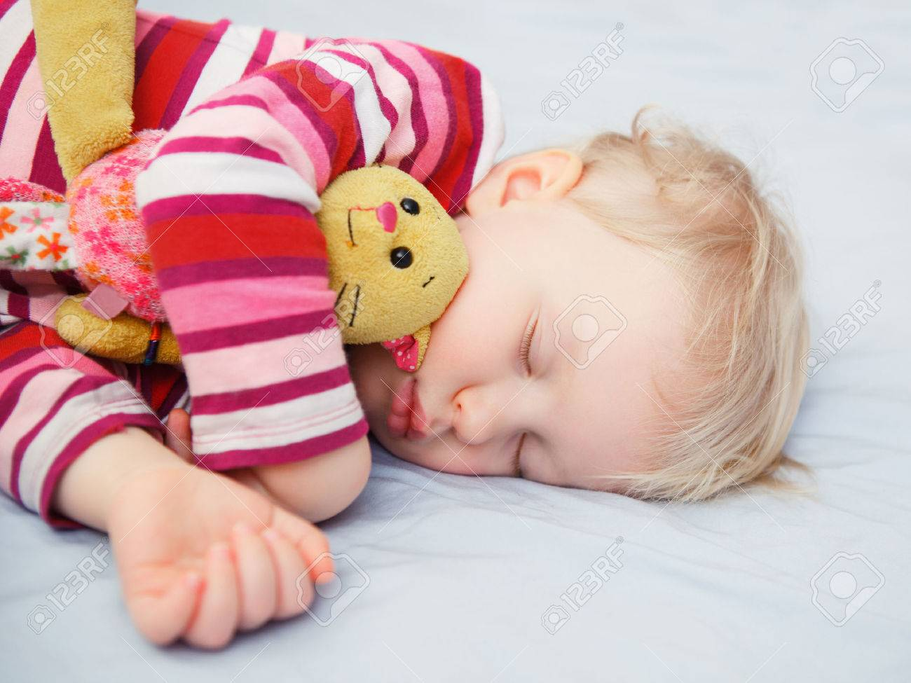 Closeup portrait of a cute adorable white blond Caucasian baby child toddler sleeping dreaming, lying on a bed with comforter toy, indoor - 36810336