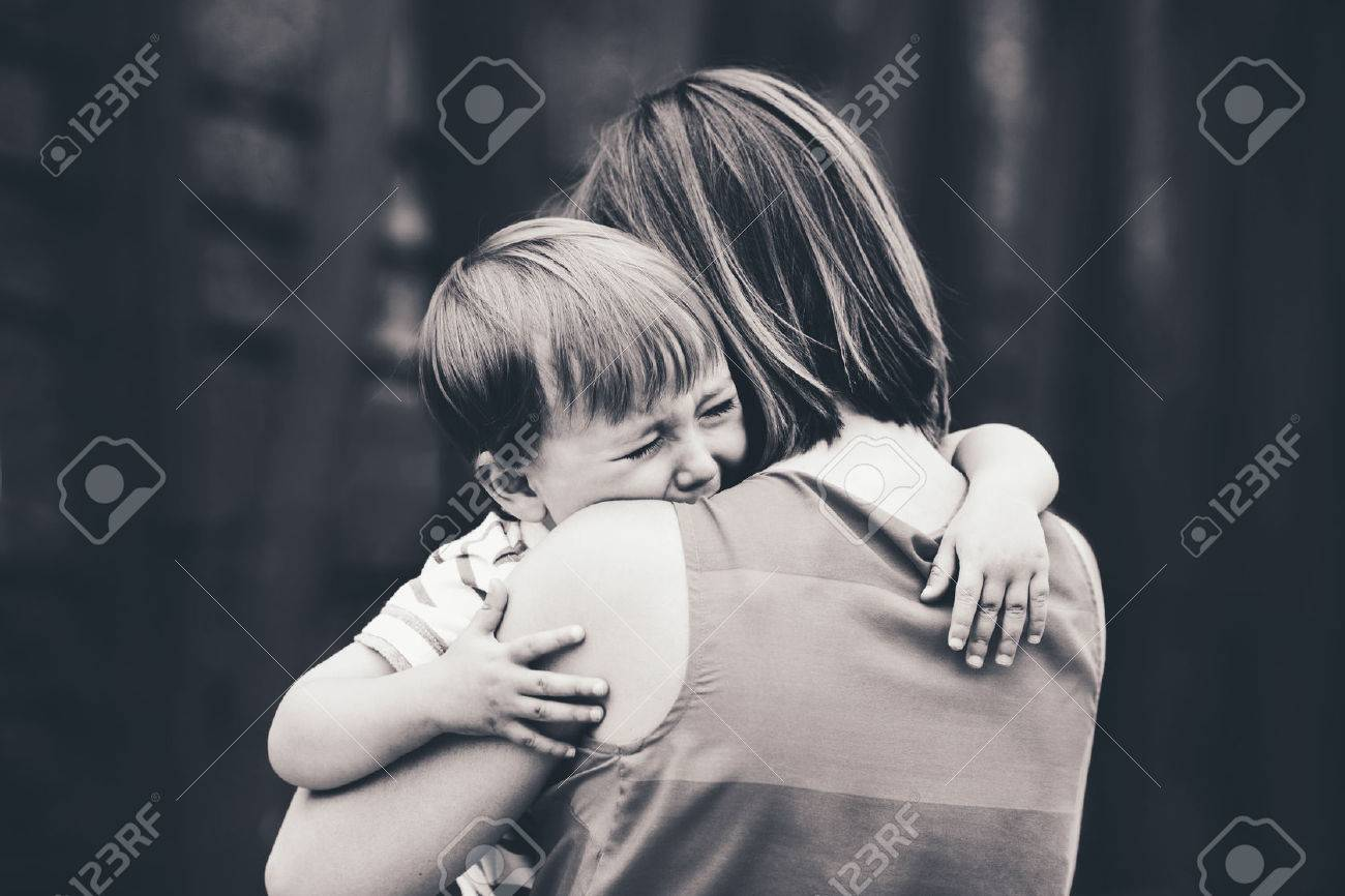 Black and white portrait of young Caucasian woman mother comforting her crying little toddler boy son outside in park on summer day, parenthood lifestyle concept - 64549777