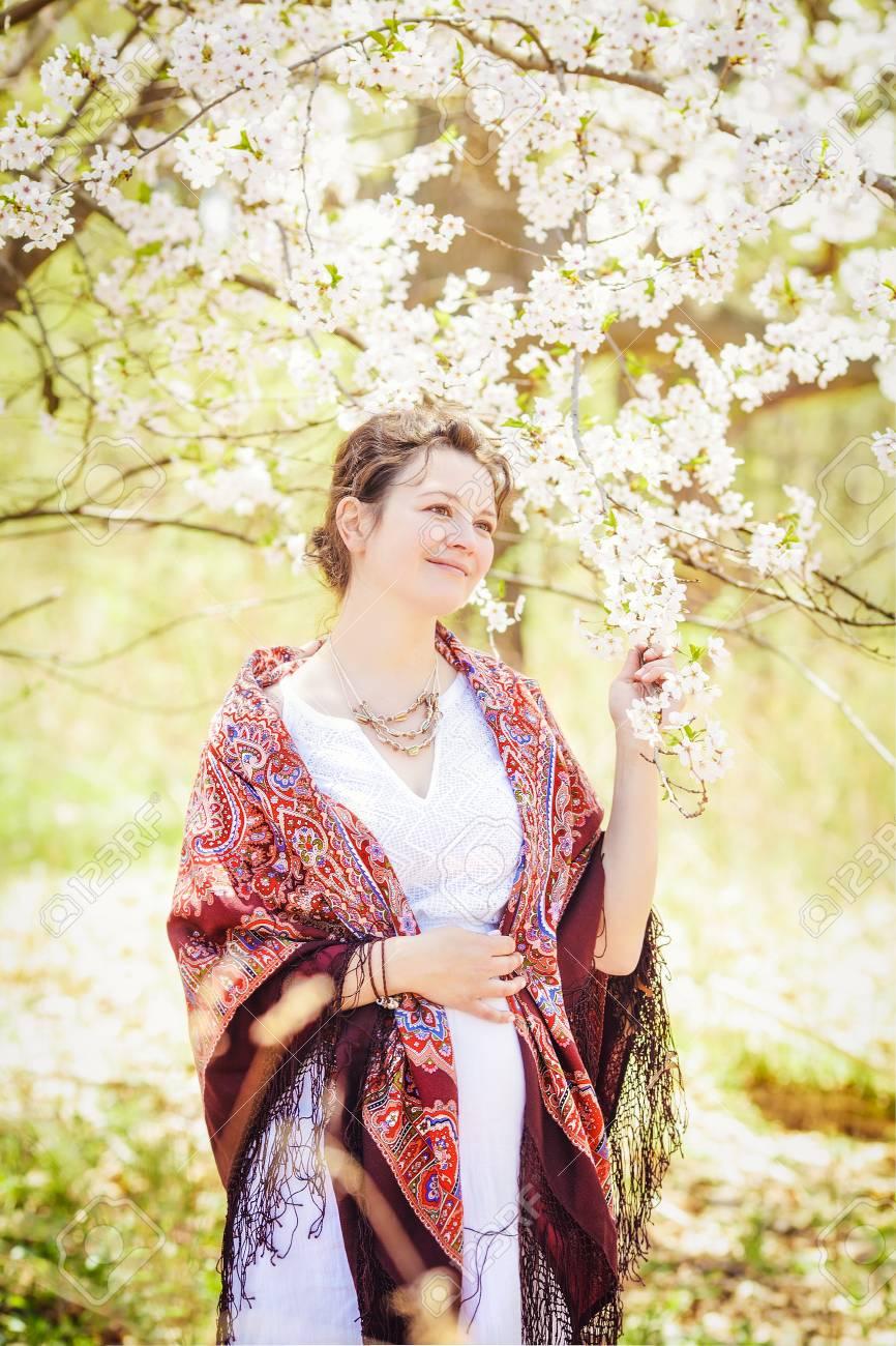 b4d6fcd78 Retrato De La Mujer Caucásica Embarazada De La Chica Joven En El Vestido  Blanco Con La Bufanda étnica Colorida Del Mantón Que Se Coloca En Parque  Afuera En ...